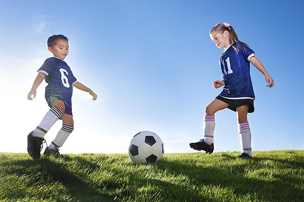 young boy and girl playing soccer on soccer field with ball