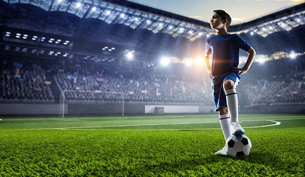 little kid soccer player standing in stadium with one foot on soccer ball