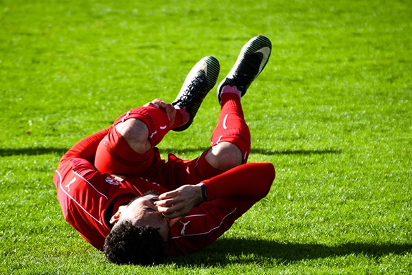 soccer player laying on the ground while holding his shin guard with his hands