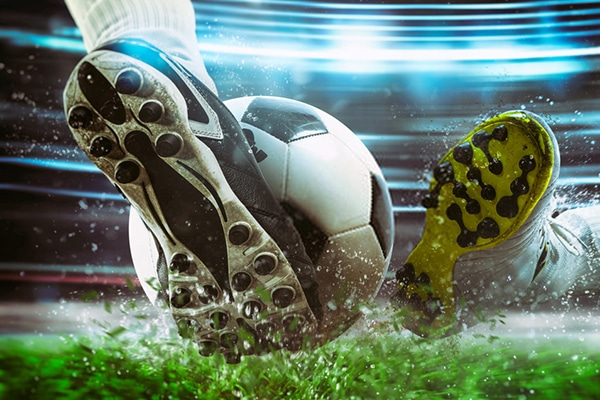 close up of a soccer cleat hitting the ball with power