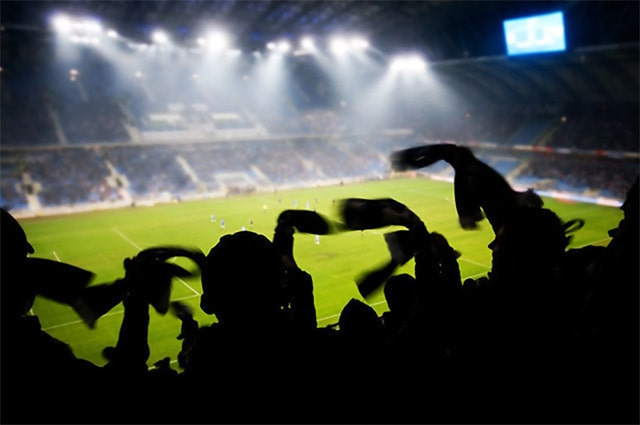 Silhouettes of fans celebrating a goal on soccer