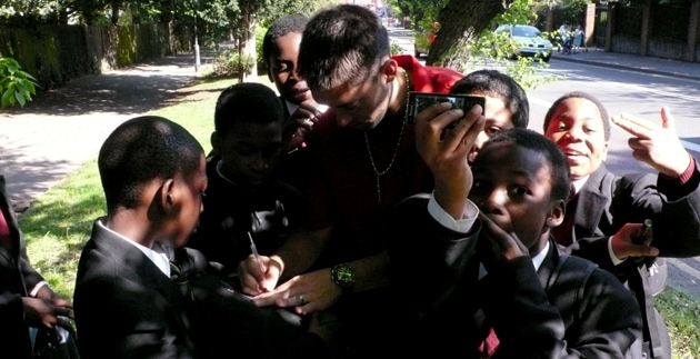 Clint Dempsey signing autographs to kids