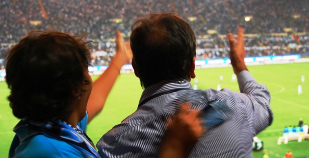two people watching soccer in stadium